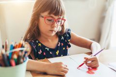 Child in glasses drawing royalty free stock photo