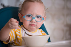 Child with glasses eating porridge. And unhappy looking at the spoon Stock Photography