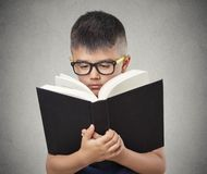 Child with glasses reading book Stock Images