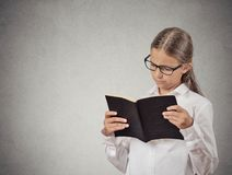 Child with glasses reading book stock image