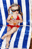 Child in glasses and red bikini drink juice. Little girl in glasses and red bikini drink orange juice Royalty Free Stock Photo