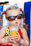 Child in glasses and red bikini drink juice. Stock Photos