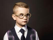 Child in glasses standing by the school board Stock Photo