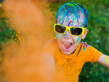 The child in glasses throws paint holi stock photo