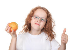 Child in glasses and white t-shirt eating an apple. Royalty Free Stock Images