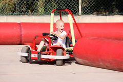 Child on go kart. A caucasian child undergoing chemotherapy treatmant due to cancer having fun on a go cart at a fun fair Stock Image