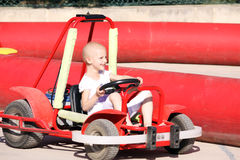 Child on go kart. A caucasian child undergoing cancer teatmant having fun on a go kart at a fun fair Stock Images