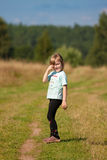 Child goes on a country road. Royalty Free Stock Photo