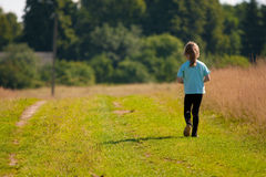 Child goes on a country road. Royalty Free Stock Photos