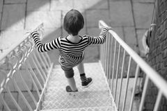 The child. Goes down the metal stairs stock image