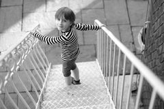 The child. Goes down the metal stairs royalty free stock photography