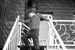 The child. Goes down the metal stairs stock photo