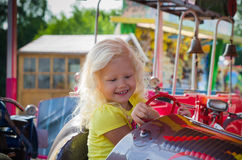 Child goes for a drive on a children's attraction Stock Images