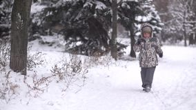 Child goes on a footpath. Child goes on snow-covered trail stock footage
