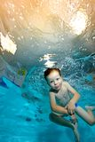 The child goes in for sports and swims underwater against the background of yellow lights. Portrait. Shooting underwater from the bottom. Vertical view Royalty Free Stock Images