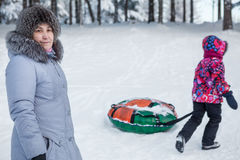 Child goes tubing with toboggan while mother looks at camera Royalty Free Stock Photo