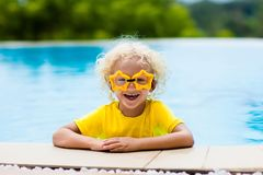 Child with goggles in swimming pool. Kids swim. Child with goggles in swimming pool. Blond curly little boy learning to swim in outdoor pool of tropical resort stock photos