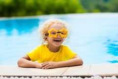 Child with goggles in swimming pool. Kids swim. Child with goggles in swimming pool. Blond curly little boy learning to swim in outdoor pool of tropical resort stock photo