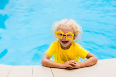 Child with goggles in swimming pool. Kids swim. Royalty Free Stock Photos