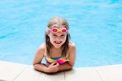 Child with goggles in swimming pool. Kids swim. Royalty Free Stock Photography