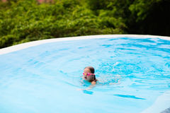 Child with goggles in swimming pool. Kids swim. Stock Photo