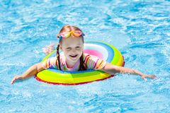 Child in swimming pool. Kids swim. Water play. Child with goggles in swimming pool. Little girl learning to swim and dive in outdoor pool of tropical resort stock photo