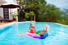 Child in swimming pool. Kids swim. Water play. Child with goggles in swimming pool. Little girl learning to swim and dive in outdoor pool of tropical resort royalty free stock image