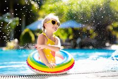 Child in swimming pool. Kids swim. Water play. stock photos
