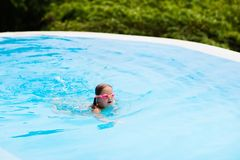 Child with goggles in swimming pool. Kids swim. Child with goggles in swimming pool. Little girl learning to swim and dive in outdoor pool of tropical resort stock photography