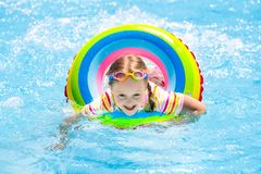 Child in swimming pool. Kids swim. Water play. Child with goggles in swimming pool. Little girl learning to swim and dive in outdoor pool of tropical resort royalty free stock photos