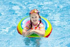 Child in swimming pool. Kids swim. Water play. Child with goggles in swimming pool. Little girl learning to swim and dive in outdoor pool of tropical resort royalty free stock photography