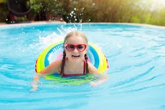 Child in swimming pool. Kids swim. Water play. Child with goggles in swimming pool. Little girl learning to swim and dive in outdoor pool of tropical resort royalty free stock images