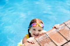 Child with goggles in swimming pool. Kids swim. Child with goggles in swimming pool. Little girl learning to swim in outdoor pool of tropical resort. Swimming stock photos