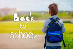 Child going back to school with backpack on green nature background with text Back to school. Back view Royalty Free Stock Photos