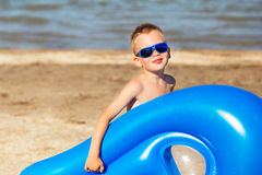Child is going to swim in the sea with a swimming mattress. Little kid holding an inflatable mattress on the beach on hot summer day. Smiling boy playing on the Stock Photo