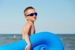Child is going to swim in the sea with swimming mattress. Little kid holding an inflatable mattress on the beach on hot summer day. Smiling boy playing on the Royalty Free Stock Images