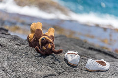 Child is gone. Plush toy dog and white shoes at beach Stock Photography