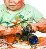 Child is grabbing some paint using fingers Royalty Free Stock Photo