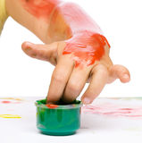 Child is grabbing some paint using fingers. Over white stock images