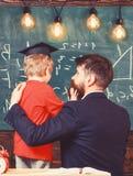 Child in graduate cap listening teacher, chalkboard on background, rear view. Teacher with beard, father hugs little son stock photo