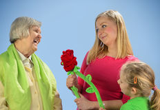 Child and grandchild give a gift senior woman. Royalty Free Stock Image