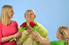 Child and grandchild give a gift senior woman. Stock Image
