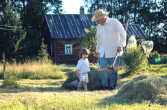 Child and grandfather rural field Royalty Free Stock Photos