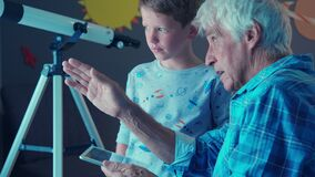 Child with grandfather using digital tablet to see the constellations