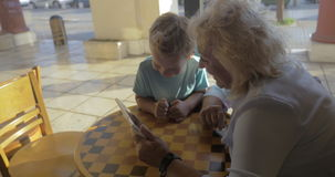Child and grandma using tablet PC in cafe. Grandmother and grandson spending time on playing with touch pad in city cafe. They have good time together stock video