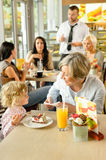 Child with grandmother at cafe eating cake. Sitting dessert restaurant Royalty Free Stock Images