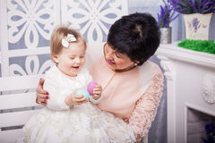 Child and grandmother with Easter eggs Stock Photo