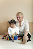 Child and grandmother reading Stock Images