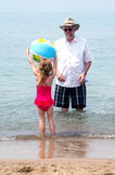 Child and grandpa playing at the beach Royalty Free Stock Photos