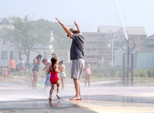 Child and grandpa playing at the whirlpool fountains Royalty Free Stock Images